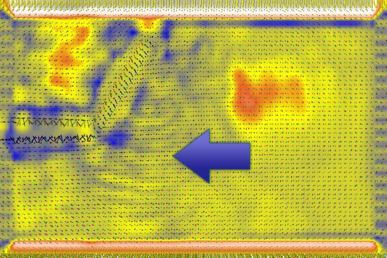 Nach oben abbiegender Riss im Aluminiumoxid. Eine neue Visualisierungsmethode macht Störungen im elektrischen Feld der Dipole sichtbar. Ausgehend von der Riss-Spitze breitet sich eine wellenförmige Störung aus, wie der Pfeil verdeutlicht.